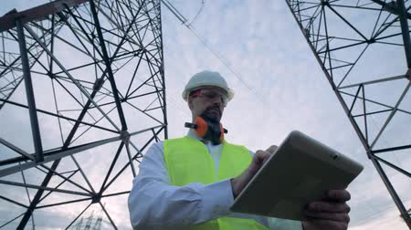 producing energy : Male technician is browsing a computer while being near electricity towers