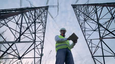 producing energy : Two tall electricity towers and a male inspector working between them