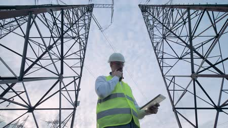 producing energy : Male engineer is operating a tablet while standing between power line towers Stock Footage