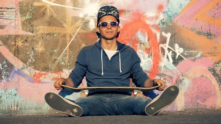 dinlenmek : A smiling skater is twisting his board while sitting beside a graffiti wall Stok Video