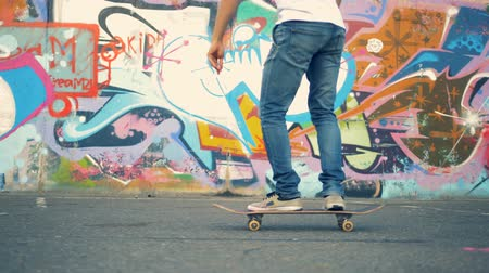 grafiti : Male rider stands up on a skateboard and starts moving Wideo