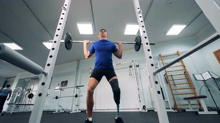 paralympics : Disabled person squatting with a barbell, bottom view. Stock Footage