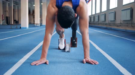 paralympics : Sprinter with prosthesis stands on a start, close up.
