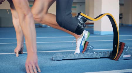 athletes foot : A runner sprints with a prosthetic leg, side view.