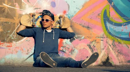 dinlenmek : Young man in streetwear is sitting on the ground with a skateboard behind his head