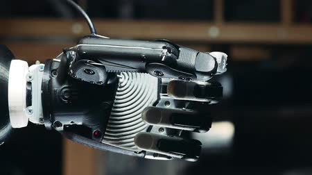 робот : Fist of a robotic arm is clenching while its getting lowered