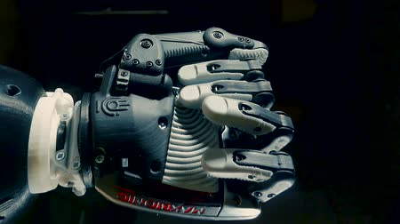 рука : Fist of a cybernetic arm is clenching and unclenching