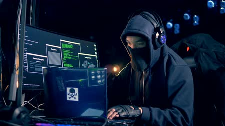 lopás : Male hacker in a hoodie is operating computers Stock mozgókép