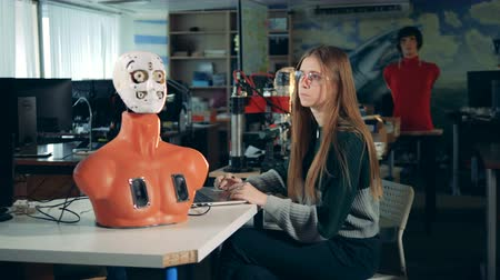 ilerici : Upper half of a cyborgs body and a young woman operating a laptop Stok Video
