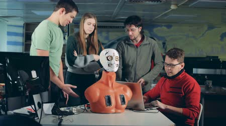 ilerici : Team of engineers are having a discussion over a human-like robot