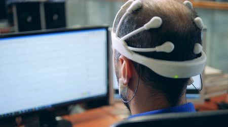 neuro : Monitor with information transmitted from an EEG headset put on a man Stock Footage
