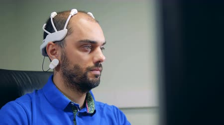 neuro : A man in a brainwave scanning headset is operating a computer