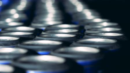 ón : Close up of tin bottoms of beer cans while moving
