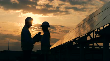 energetyka : A female and a male engineers talking in the rays of setting sun near a solar panel. Alternative energy concept Wideo