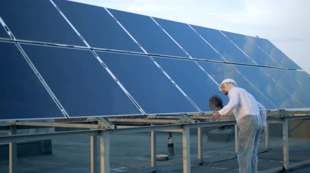 energetyka : Male specialist in protection clothes is cleaning a solar panel. Alternative energy concept.