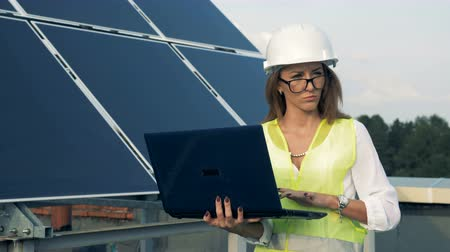 energetyka : Solar panels and a female engineer going along it with a laptop. Alternative energy concept.