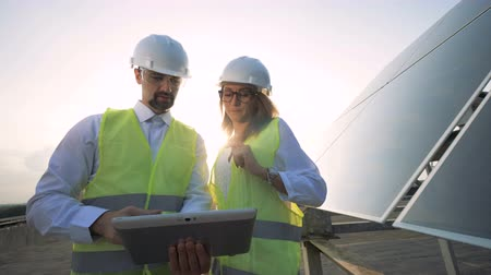 energetyka : Female solar engineer is approaching her male colleague and showing construction project. Alternative energy concept