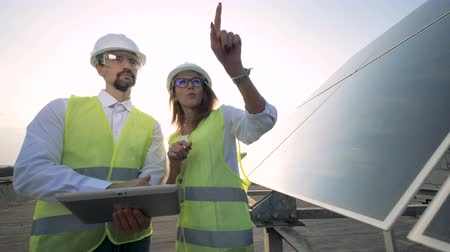 energetyka : Female architect, engineer talking with male engineer near solar battery. Alternative energy concept Wideo