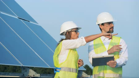 energetyka : Renewable energy concept. Two energetics employees are walking along a solar construction with a tablet