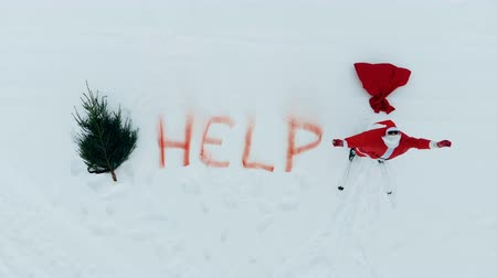 escrito : Snow wides with help written on them and Santa Claus crying