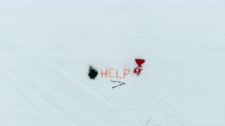 sos : Snowy field with axed fir tree, skis and Santa Claus shouting for help