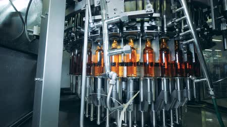 distillation : Plant machine works, moving bottles with alcohol, close up.