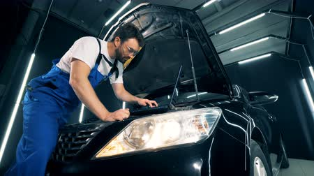 motorháztető : Parts of an automobile are getting checked by a technician