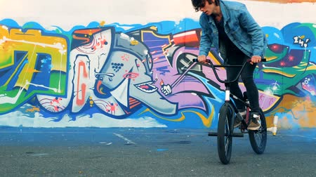 paten yapma : A teenager jumps on a bike on a wall background, slow motion.