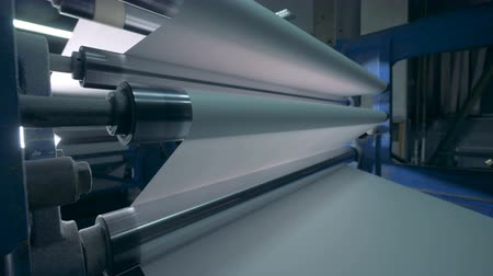 ofset : Printing machine and white paper rolling through it