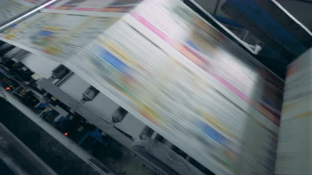 üreten : Coloured paper is moving through a printing machine at high speed Stok Video