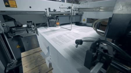 nakladatelství : Printed paper is getting dragged into an industrial machine
