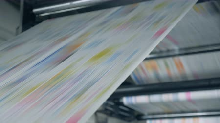 журналистика : Close up of coloured paper moving through the factory press