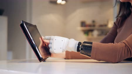 substitute : Tablet computer is getting operated by a female with a bionic arm Stock Footage