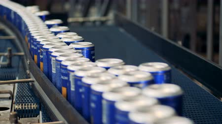 консервированный : Lots of cans with beer on a factory conveyor, close up. Стоковые видеозаписи