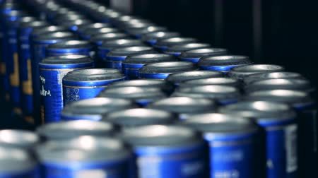 drink cans : Metal cans with beer moving in rows, close up.