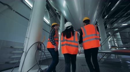 fermenting : Brewery workers walking in a facility room, back view.