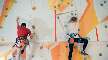 dağcı : People climbing on a training wall, close up. Stok Video