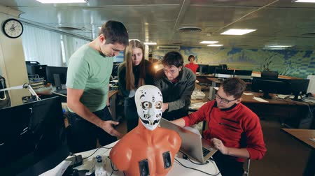 microelectronic : Group of engineers fix a robot, close up.