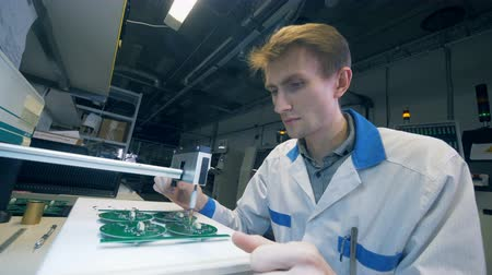 naukowiec : Electronic boards are getting made by a male lab worker