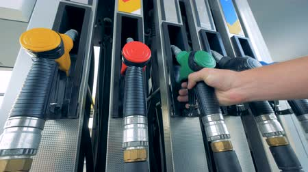 benzine : Petrol pistol with green handle is being inserted into the pump