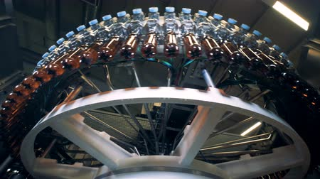 functioning : Revolving transporter is displacing bottles with beer Stock Footage