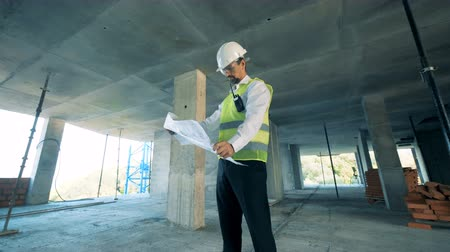 construtor : Engineer looks at a building layout, close up.