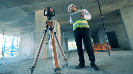 construtor : A constructor talks, using a walkie-talkie at a site, close up.