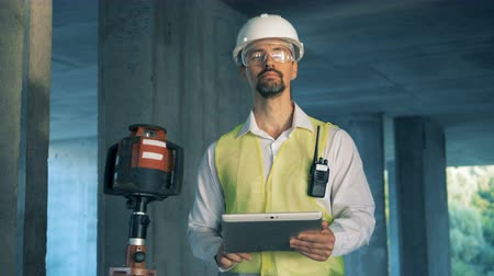 construtor : A worker types on a tablet and smiles at camera, close up.