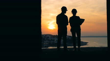 construtor : People working with a blueprint on a sunset background, back view.
