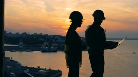 construtor : Builders work with a laptop on a sunset background, close up.