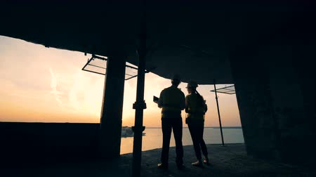 квартиры : Builders look at a cityscape on a sunset background, back view.