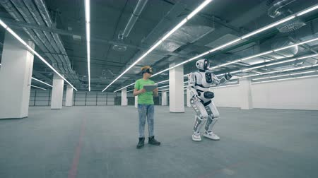 ilerici : Empty storage unit with a boy in VR-glasses and a moving robot Stok Video