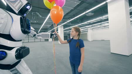 droid : Robot gives balloons and its hand to a girl in a storage unit Stock Footage