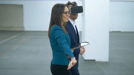 realty : Female estate agent is showing an empty hall to a businessman in VR-glasses. Commercial real estate. Stock Footage